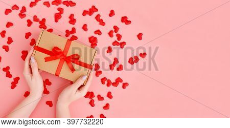 Females Hands Holding Gift Box With Hearts Confetti Decoration On Pink Background. Christmas, New Ye