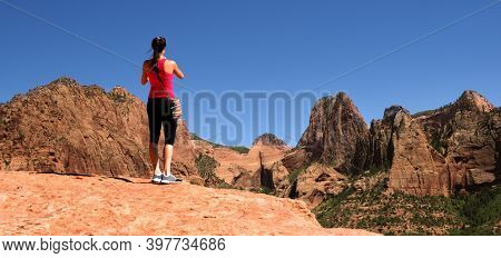 Fit young woman taking a cell phone picture of the geologic features of the southwest USA. Panoramic format.