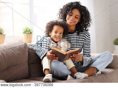 Happy Ethnic Family: Delighted African American Mother Sitting On Couch And Reading Interesting Book