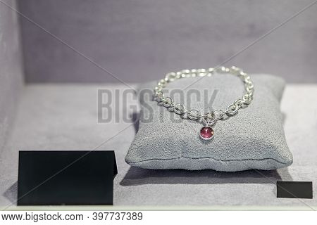 Elegant White Gold Or Silver Necklace With Pink Gemstone On Grey Pillow Background. Small Charm Acce