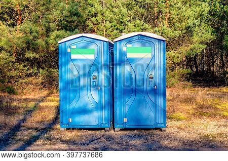 Two Blue Plastic Toilet Cabins. Public Toilet In The City Park. Chemical Toilet House On A Construct