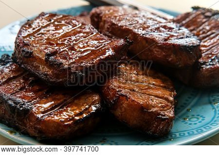Marinated Char-grilled Pork Chops With Grill Marks On A Server Plate