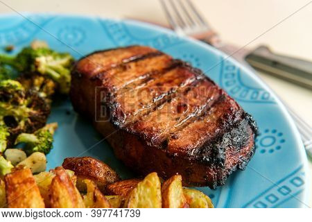 Marinated Char-grilled Pork Chops With Grill Marks Side Of Home Fries And Broiled Broccoli