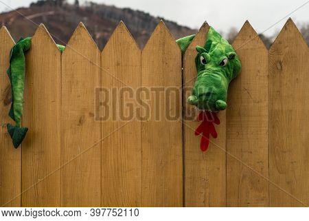 Serpent Gorynych, Character In Slavic Folk Tales. Toy Green Snake On Fence. Fairy-tale Villain.