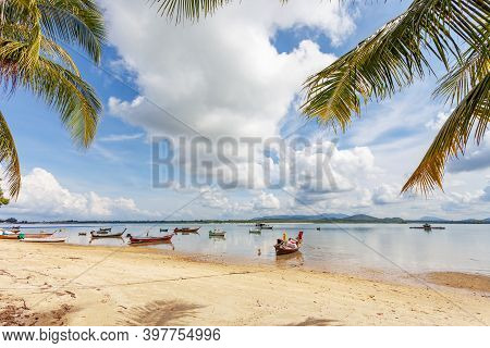 Traditional Longtail Boats Parking On The Beach With Coconut Palm Trees Frame In Phuket Island Beaut
