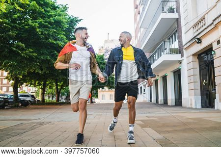 Gay Couple Holding Their Hands And Running Together.