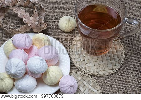 Homemade Meringue Kisses And Tea Cup. Meringue Cookies On Natural Sackcloth Background.