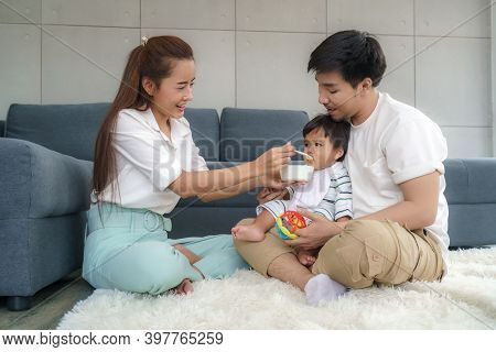 Asian Mother Feeding His 6 Months Old Baby Boy With Solid Food With Spoon And Father Sitting Near To