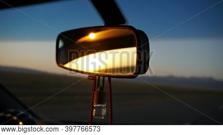 The Rear View Mirror Of The Car And Dawn. Orange Dawn Over The Hills. The Car Is Going At High Speed