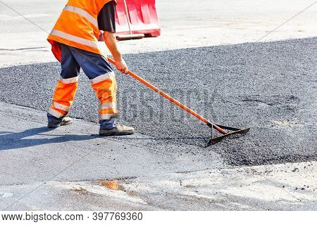 While Repairing The Road, The Road Builder Levels The Fresh Asphalt With A Metal Level Against The B