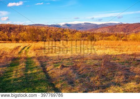Sunny Evening In Mountainous Countryside. Beautiful Rural Landscape In Springtime. Country Road Thro
