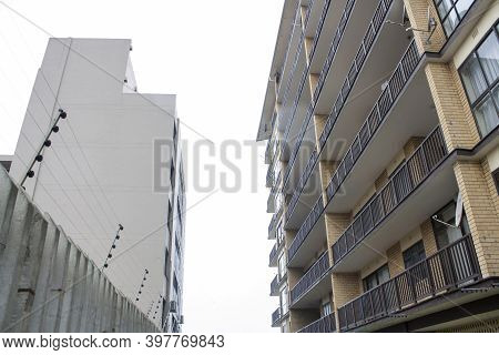 Tall Residential Skyscraper With Electric Fencing Against Cloudy Sky