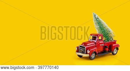 Red Retro Toy Truck With Christmas Tree On Truck Body On Yellow Background. Delivery, Christmas, New