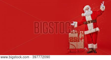 Full length portrait of the good old Santa Claus carrying gifts on a sleigh under a snowfall on a red background. Delivery service of Santa Claus.