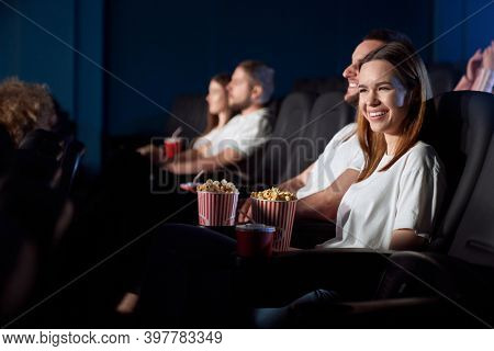 Selective Focus Of Young Girl Laughing From Weird Situation, Watching Comedy In Cinema. Side View Of