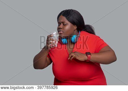 Young Dark-skinned Woman In Headphones Feeling Thirsty