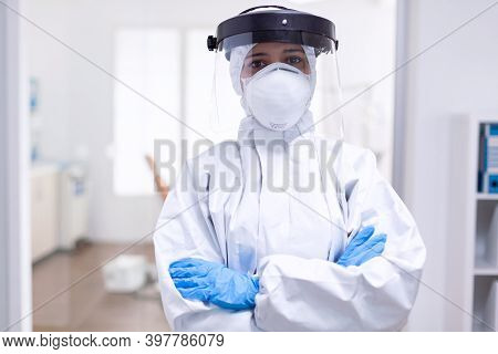Stressed Doctor With Arms Crossed In Hazmat Suit During Coronavirus Outbreak. Medical Personal Dress