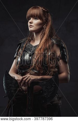 Portrait Of Pretty And At The Same Time Dangerous Nordic Female Fighter Holding Huge Axe In Dark Bac