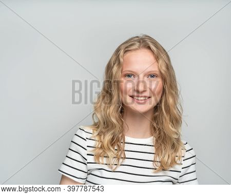 Beautiful Young Smiling Clever Blonde Woman Without Makeup On White Wall. Pretty Female With Curly H