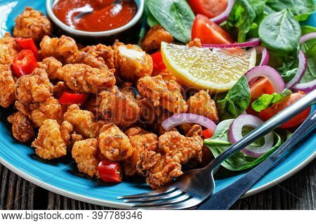 Crispy Popcorn Chicken American Snack Served On A Blue Plate With Ketchup And Salad Of Baby Spinach,