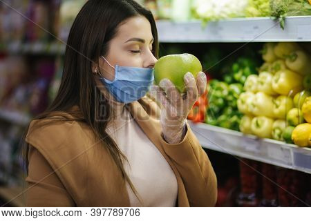 Happy Woman In Protective Mask Taking Fresh Vegetables While Standing By Groceries In Supermarket. B