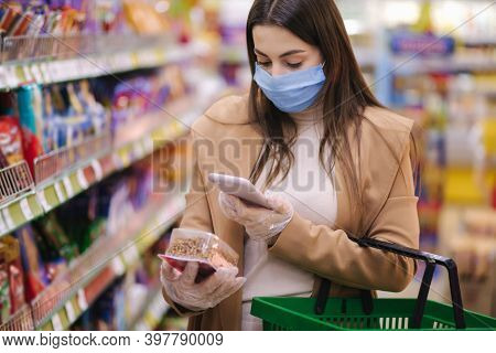 Woman In Protective Mask And Gloves Scan Label With Price Using Phone At Goods While Standing In Sup
