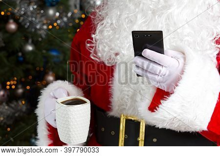Santa Claus Holding White Mug With Coffee And Smartphone In His Hand, Close-up. Mobile Phone And Cof