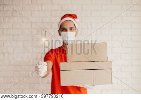 Happy Young Delivery Man In Medical Face Mask, Protective Gloves Carry Cardboard Boxes And Sparkler