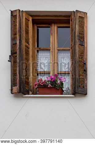 Pink Flowers In A Pot On Window Sill. Residential Building Window With Brown Wooden Shutters In Gree