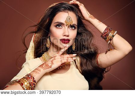 Wavy Hair. Portrait Of Beautiful Woman With Indian Jewelry. Young Brunette Model With Traditional In