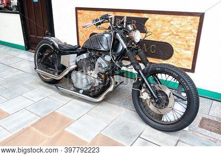 Beppu, Kyushu, Japan, June 21, 2017: A Black Vintage Yamaha Motorcycle Stands At The Entrance To The