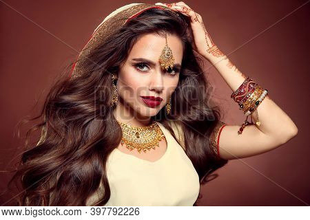 Wavy Hair. Portrait Of Beautiful Girl With Indian Jewelry. Young Woman Model With Kundan Golden Bijo