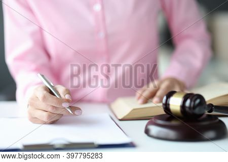 Woman Judge Writing In Documents With Ballpoint Pen Near Hammer Of Courthouse. Consideration Of Admi