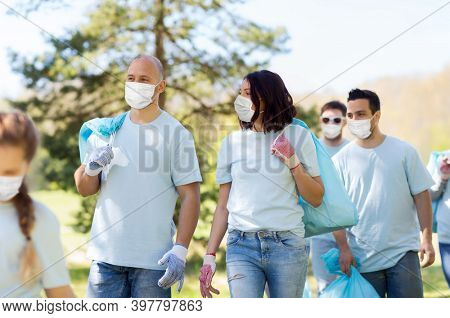 volunteering, health and ecology concept - group of volunteers wearing face protective medical mask for protection from virus disease with garbage bags walking in park