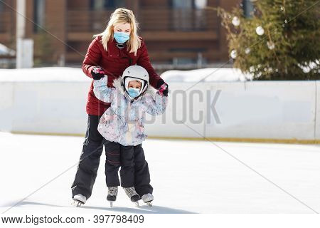 Young Mother Teaching Her Little Daughter Ice Skating At Outdoor Skating Rink. Family Wearing A Medi