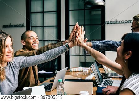 Team of business people giving a high five