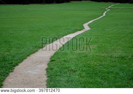 Threshing Gravel Road Through A Green Meadow Without Vegetation Waves With Zig Zag Like A Snake. Bei