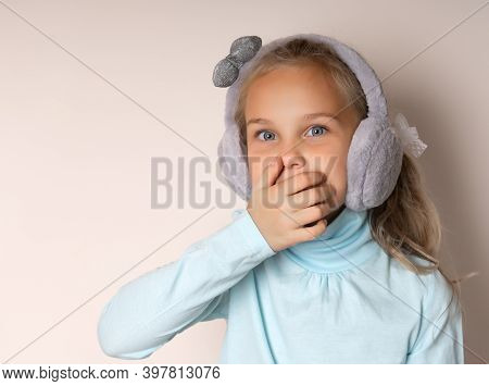 Little Cute Toothless Girl Fooling Around In Warm Fur Headphones On A Light Background