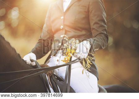 A Rider Sitting In The Saddle On A Black Horse Is Holding A Bridle Rein And A Bouquet Of Summer Fiel