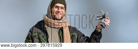 Cheerful Man In Parka Holding Gloves And Smiling On Grey