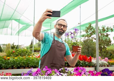 Bearded Male Gardener Taking Selfie With Potted Petunia. Caucasian Pretty Blonde Woman Holding Smart