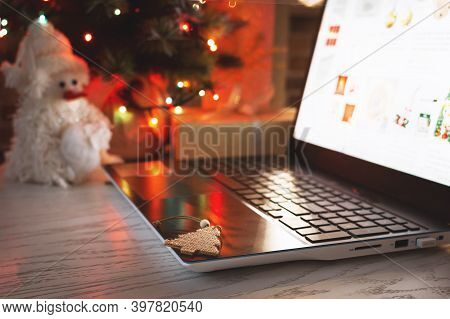 Christmas Shopping Online. Laptop On Table At Home On The Background Of A Christmas Tree With Blurre