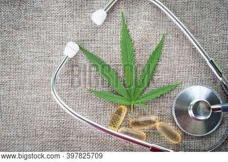 Medical Stethoscope Cannabis Leaves And Extracted Tablets Placed On A Brown Background, A Treatment