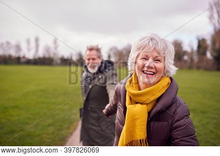 Portrait Of Loving Senior Couple Enjoying Autumn Or Winter Walk Through Park Together