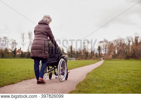 Rear View Of Senior Woman Pushing Senior Man In Wheelchair Outdoors In Fall Or Winter Park
