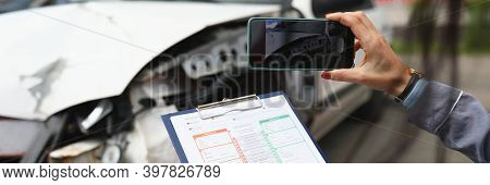 Woman Photographs A Broken Car On Smartphone And Holds Insurance Documents In Her Hands. Damage Asse