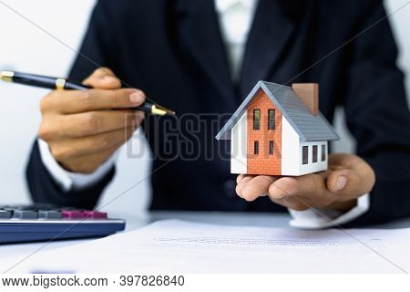 Gray Roof House On The Hands Of Businessmen Or Agents And Signing The Purchase Contract House Tradin