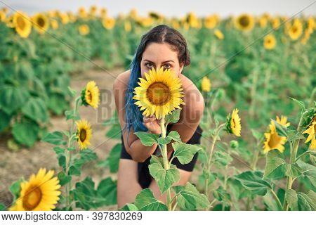 young woman hidden behind a sunflower