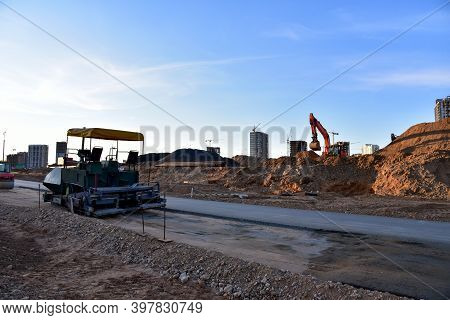 Paving Roller Machine And Excavator During Road Work. Road Roller At Construction Site For Paving Wo