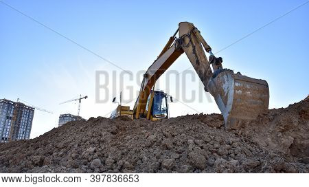 Excavator Working At Largest Construction Site. Backhoe On Earthworks. Tracked Loader Laying Externa